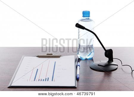 Computer microphone with documents and water on table