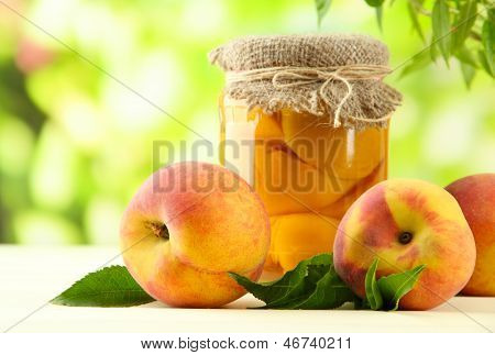 Jar of canned peaches and fresh peaches on wooden table, outside