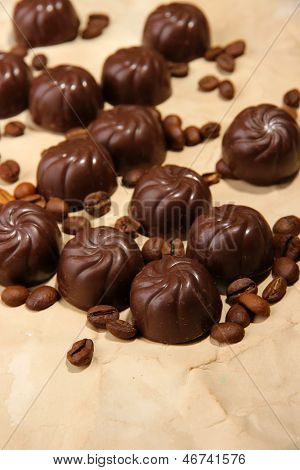 Chocolate candies and coffee beans, on beige paper background