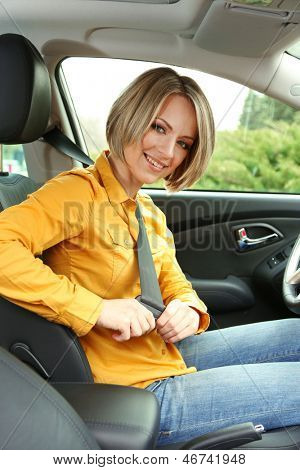 Portrait of young beautiful woman attaching seat belt in the car