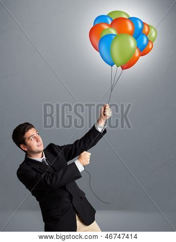 Handsome young man holding colorful balloons