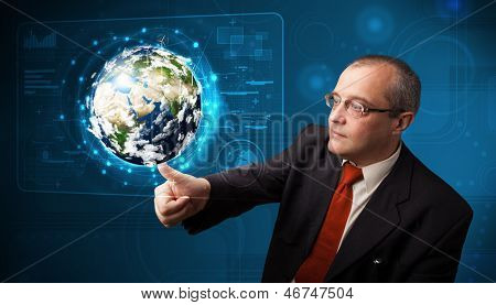 Businessman standing and touching high-tech 3d earth panel - elements of this image furnished by NASA
