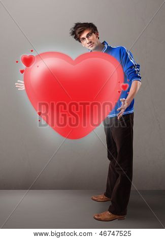 Handsome young man holding lovely 3d red heart