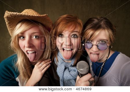 Three Young Girls With Microphone And Tongues Out