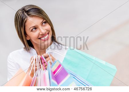 Thoughtful shopping woman looking up holding bags