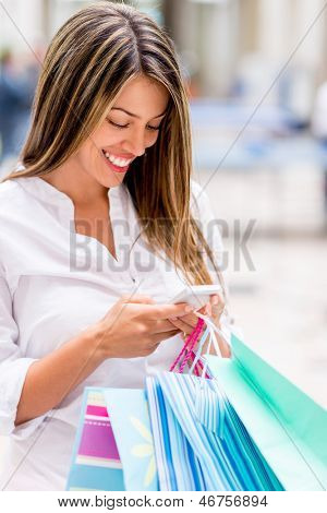 Shopping woman texting from her cell phone