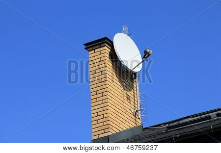 Tv satellite dish on  chimney.