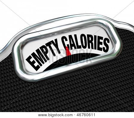The words Empty Calories on the display of a scale to illustrate the importance of eating nutritional foods for good health instead of junk or fast food such as snacks, candy or other sugary items