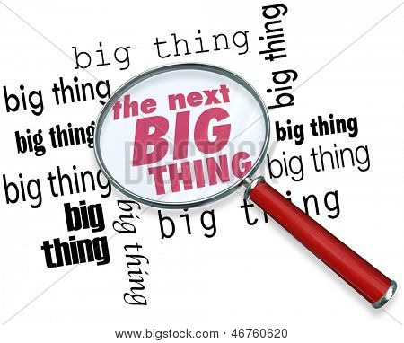 A magnifying glass on the words The Next Big Thing to illustrate finding the latest or newest trend, craze, style, fad or fashion that is popular with the public
