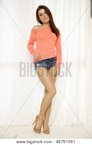 Young adult slim sexy and attractive brunette sensuality woman in orange sweater and blue jeans short against the white window