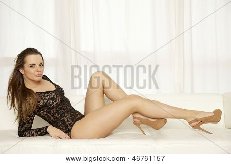 Beautiful attractive and sexy young adult sensuality brunette woman wearing black lingerie and brown shoes in white sofa on white background