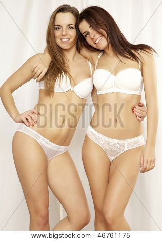 Two young adult attractive and sensuality girl friends - sexy blond and brunette in white lingerie posing on white background