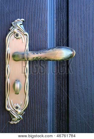 The iron doorhandle on the wooden doors