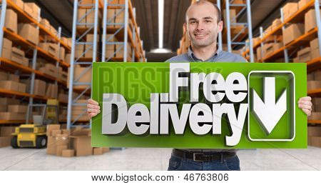 A man holding a Free delivery board in a distribution warehouse