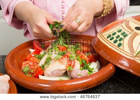 Hands of a woman cutting herbs into a traditional Moroccan tajine during Ramadan nights (Moroccan immigrant woman in modern European kitchen)