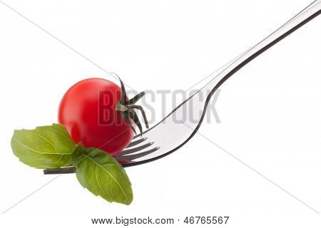 Basil leaf  and cherry tomato on fork isolated on white background cutout. Healthy eating concept.
