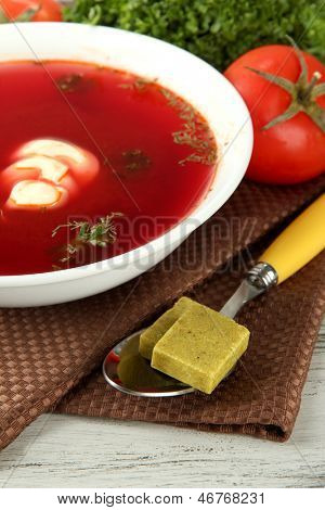 Bowl of soup with bouillon cubes on wooden table
