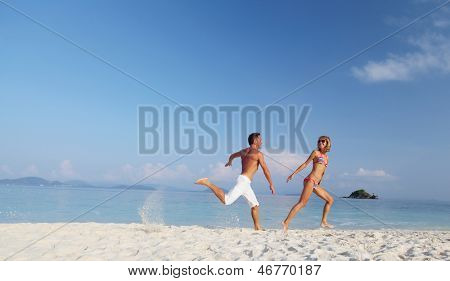Active couple running on a white sandy beach