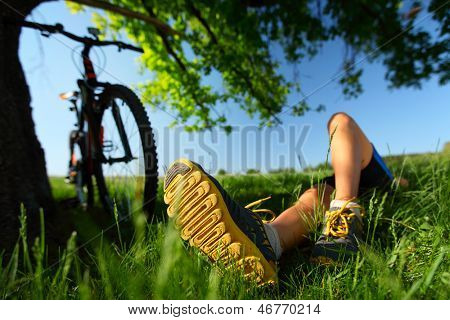 Young lady relaxing on a green meadow after cycling. Focus on a foot