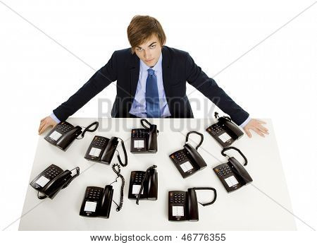 Young man in the office with a bunch telephones on his front