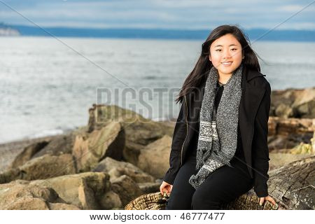 Beautiful Young Woman Sitting On Beach Driftwood