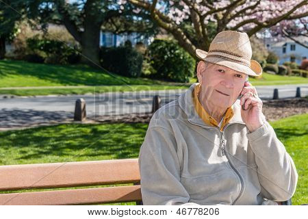 Senior Man Talking On Cell Phone In Park