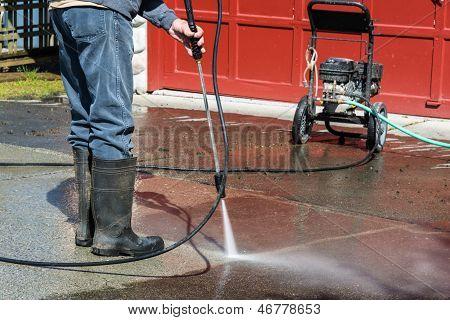 Mann, die Einfahrt mit Hochdruckreiniger reinigen