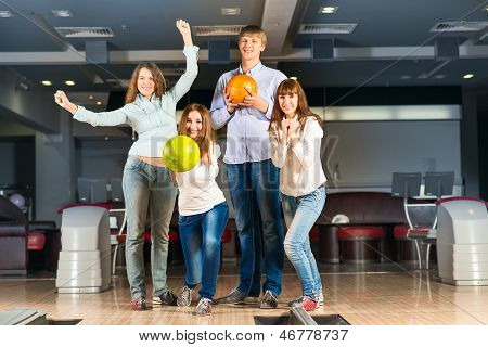 Group of young friends playing bowling