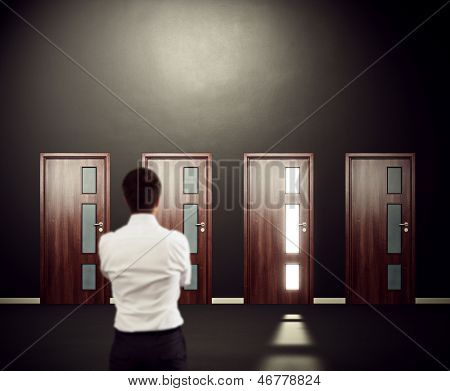 businessman looking at four doors. focus on the doors