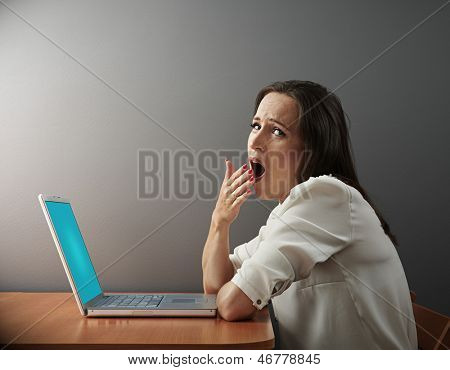 boring woman sitting with laptop and yawning