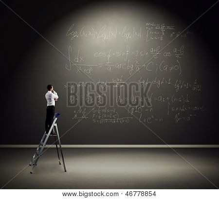 serious man standing on the stepladder and pondering over formulas