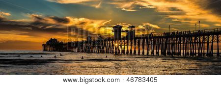 Last wave of the day - Silhouetted surfers in Oceanside California look for one last wave near the old wooden pier at sunset. Oceanside is 40 miles North of San Diego, California (USA).