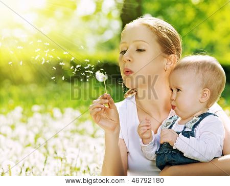 Happy Family. Mother And Baby Girl Blowing On A Dandelion Flower On The Nature