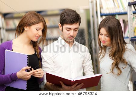 Three students reading a book together