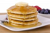 stock photo of buttermilk  - Stack of pancakes with fruits on background. Front view.