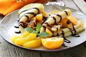 thin pancakes (crepes) with peaches and chocolate sauce