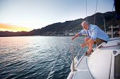 stock photo of sailing vessels  - mature retired man sailing his boat as a hobby at sunrise - JPG