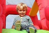foto of bouncing  - 2 year old boy smiling on an inflatable bouncy castle - JPG