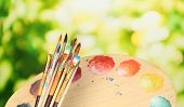 image of paint palette  - Many brush in paint on nature background - JPG