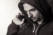 stock photo of thug  - Black and white image of a caucasian male in a hoodie holding a gun - JPG