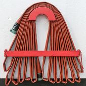 picture of firehose  - red firehose hang on the white wall - JPG