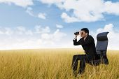 foto of binoculars  - Businessman see vision using binoculars on wheat field - JPG