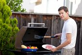foto of bbq party  - young handsome man ready for grilling meat and vegetables at his house backyard - JPG