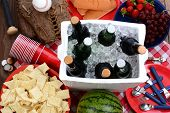 Overhead view of a picnic table, with ice chest full of beer, bowl of chips, watermelon, strawberrie