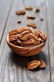 foto of pecan  - Pecan nuts in a wooden bowl closeup on wooden background - JPG