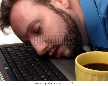 Man Asleep On Laptop With Cup Of Coffee