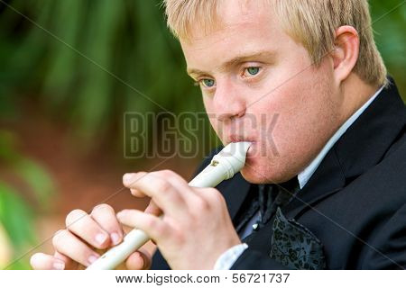Face Shot Of Disabled Boy Playing Flute.