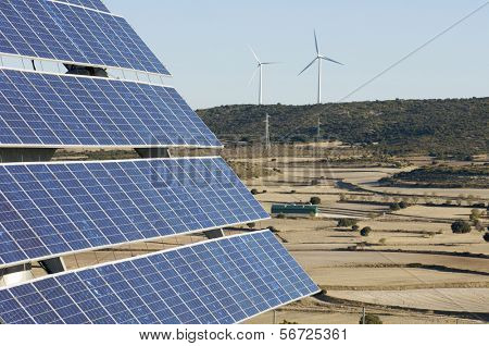 photovoltaic panels and windmills in a hill