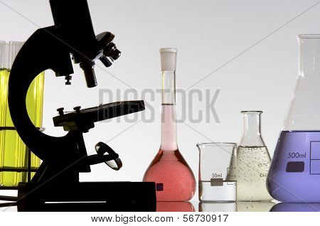 research microscope and laboratory bottles with colored liquid
