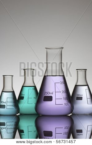 four conical glass flasks in a chemistry lab